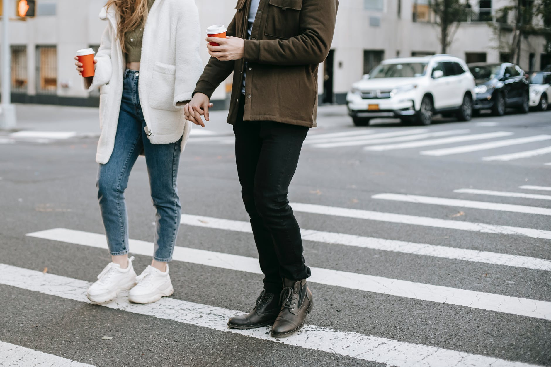 man and woman on crosswalk with paper cups